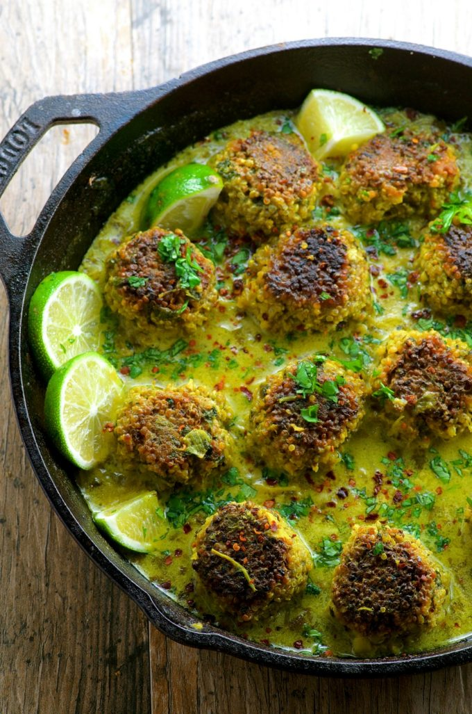 Cauliflower Quinoa Meatless Meatballs in Coconut Turmeric Broth in a cast iron pan with slices of lime