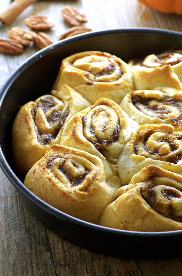 Side View of Easy Banana Pumpkin Cinnamon Rolls on a round black metal baking dish. On the background you there are some pecan a couple sticks of cinnamon.