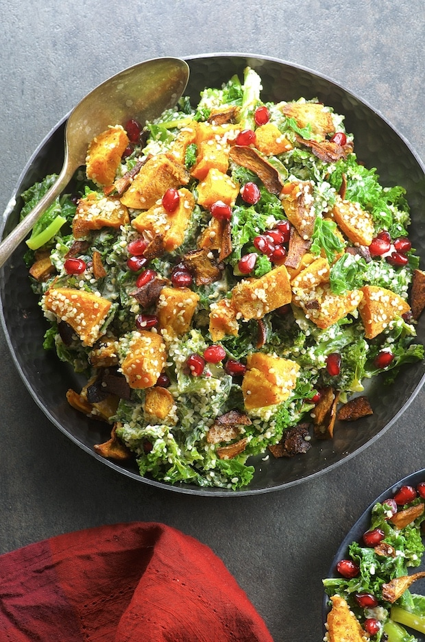 Bird's eye view of a bowl of Vegan Kale Caesar Salad With Mushroom Bacon Bits with butternut squash and Pomegranates
