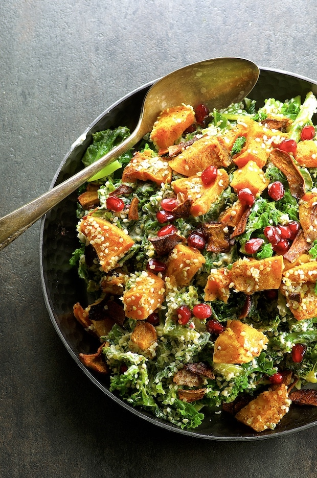 Bird's eye view of a a partial bowl of Vegan Kale Caesar Salad With Mushroom Bacon Bits with butternut squash and Pomegranates