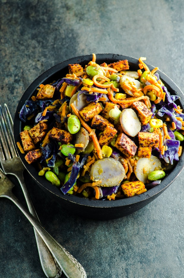 Spiralized sweet potato noodles, purple cabbage, edamame, corn, water chestnuts and tofu in a creamy peanut sauce transform this dinner bowl into a healthy vegan and vegetarian dinner.