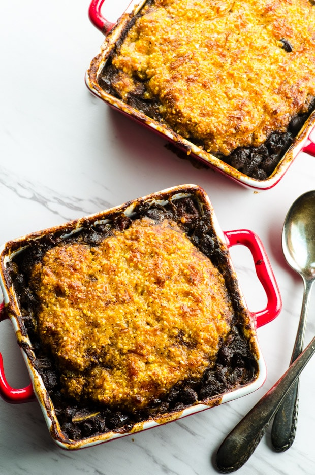 Bird's eye view of 2 square red ramekins filled with black bean vegetarian chili and topped with a homemade cheese corn bread topping. The ramekins are on top a white marble surface and there is a partial view of 2 spoons on the right hand side.