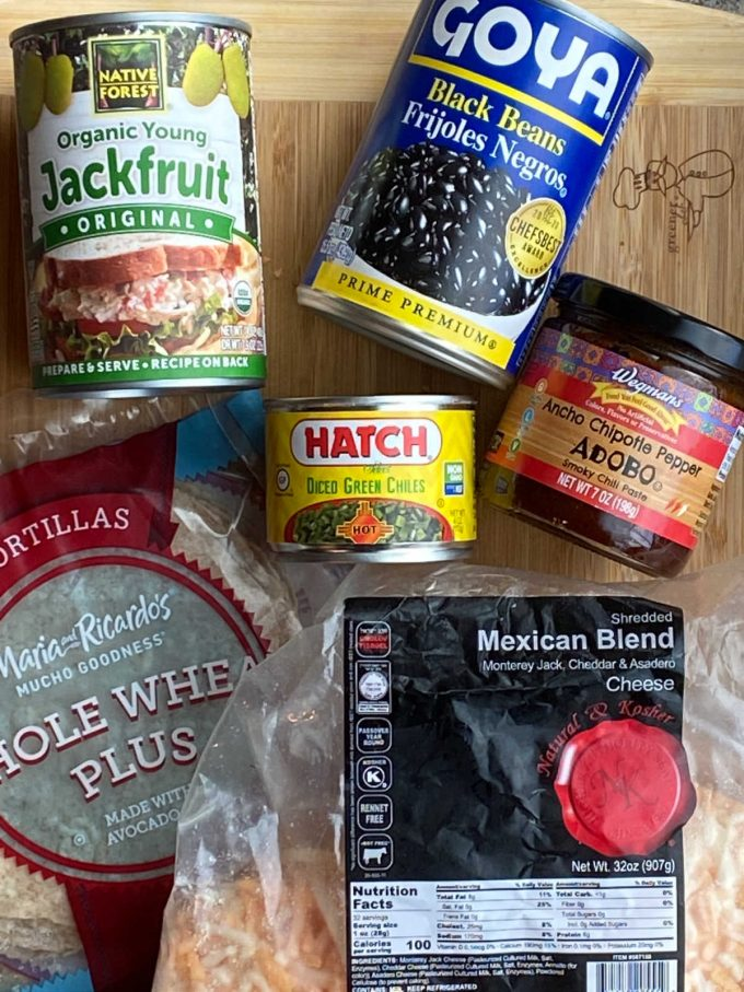 Ingredients for jack fruit enchiladas. canned jackfruit, canned black beans, canned diced chili peppers, chipotle in adobo, whole wheat tortillas and Mexican cheese blend