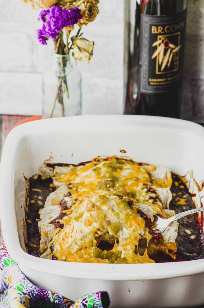Scooping a vegetarian enchilada from a white baking dish