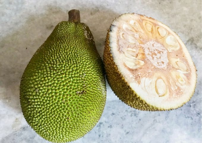 Image of a whole jackfruit and and one cut in half