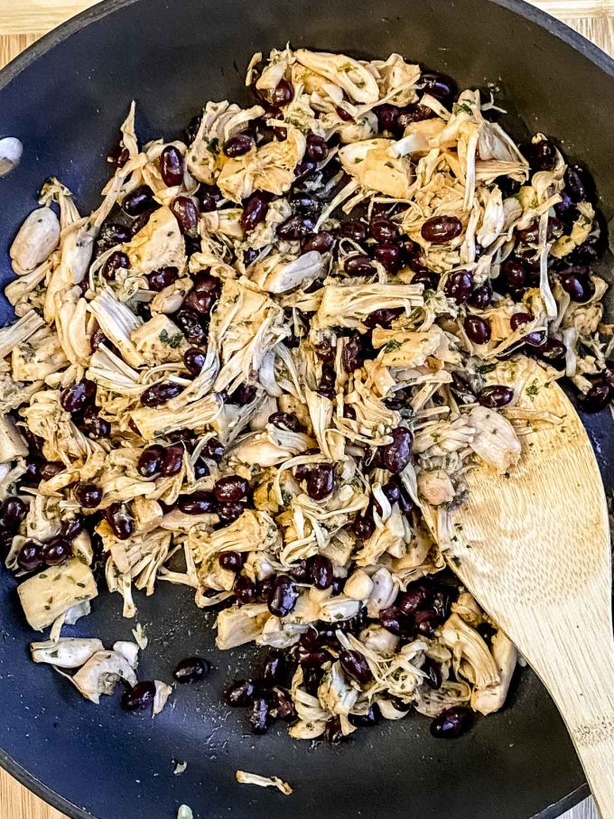 adding black beans to a skillet with jackfruit
