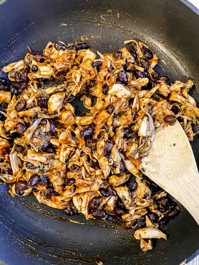 adding enchilada sauce to a pan of jackfruit and black beans