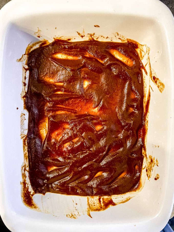 Spreading enchilada sauce at the bottom of a baking dish