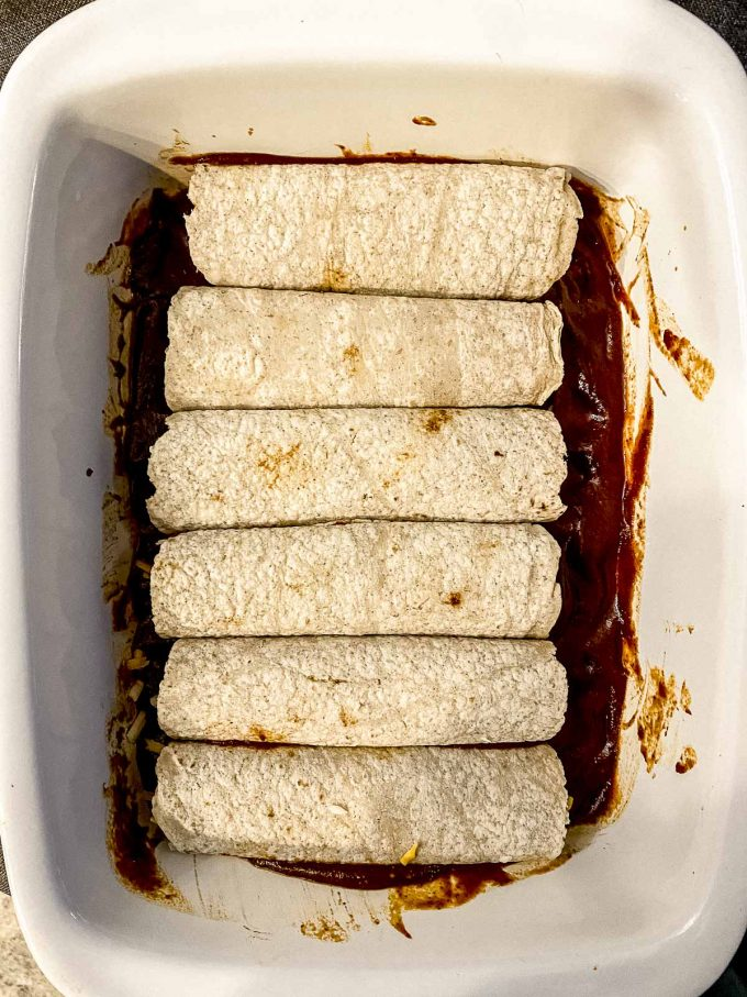 Rolled flour tortillas on baking dish with enchilada sauce
