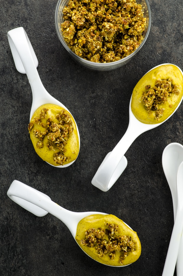 Birds eye view of golden milk cheesecake bites on white spoons with crust sprinkled on top on a black surface