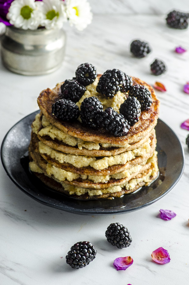 A stack of whole wheat pancakes layered with lemon cashew ricotta topped with blackberries