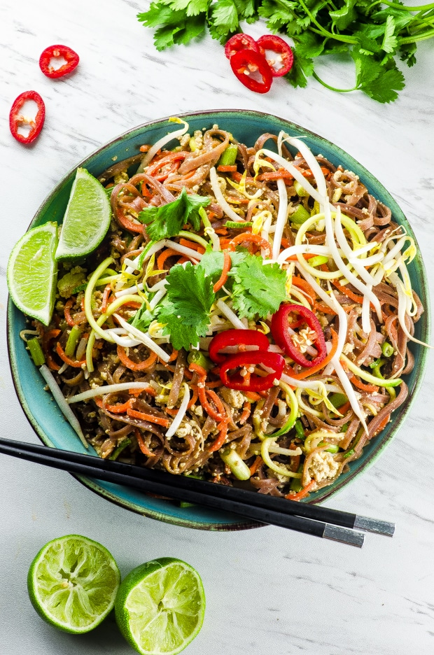 Birds eye view of the vegan pad thai salad in a blue serving bowl with chopsticks and two lime wedges