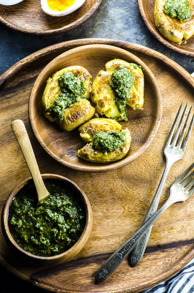 Birds eye view of three smashed potatoes with chimichurri sauce on a wooden plate, and a small wooden bowl filled with chimichurri sauce