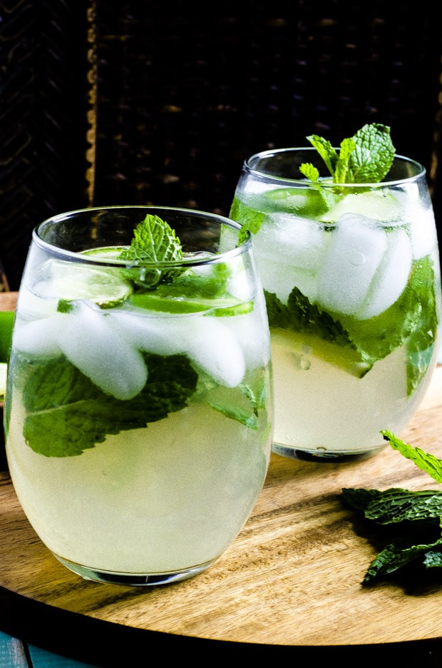 Two glasses with Jalapeno Lime Mint Ice Tea Spritzer on a wooden tray