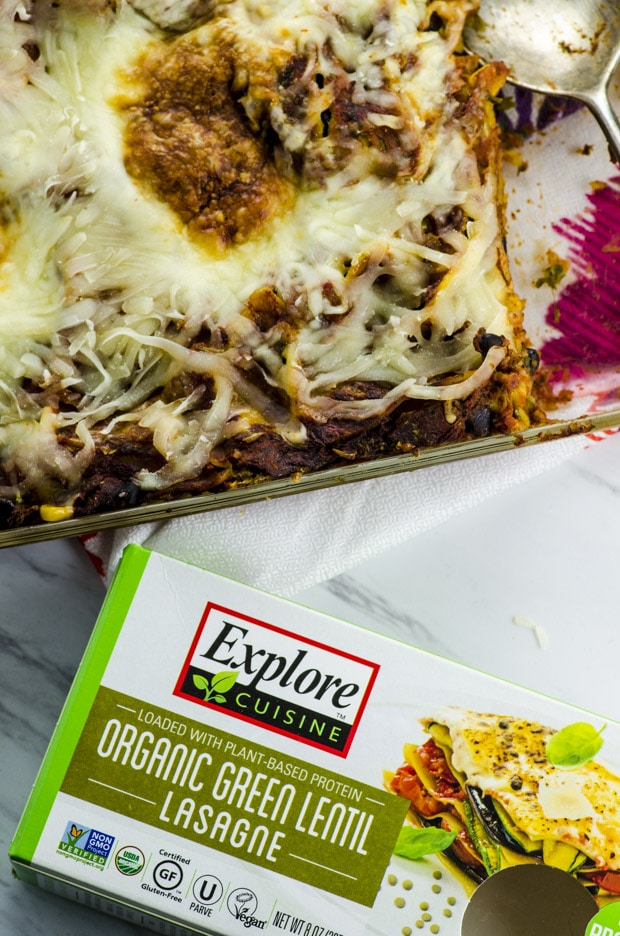 Birds eye view of theMexican lasagna in a clear baking dish with a box of Explore Cuisine green lentil lasagna sheets