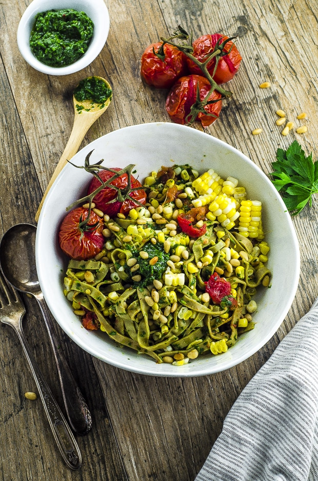 Birds eye view of the edamame pasta with chimichurri sauce on a wooden surface with a small bowl of chimichurri and three roasted tomatoes