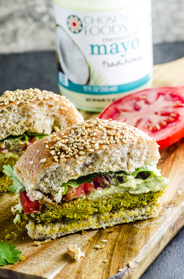 Falafel Veggie Burger With Avocado Tahini Cream on a bun, with a tomato slice and some parley leaves, sliced in half, on a wooden cutting board. In the background there is a jar of Chosend Foods Mayo