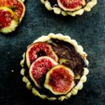 Overhead view of one chocolate truffle and fig tart
