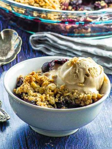Side view of a bowl filled with blueberry crumble and topped with vanilla ice cream