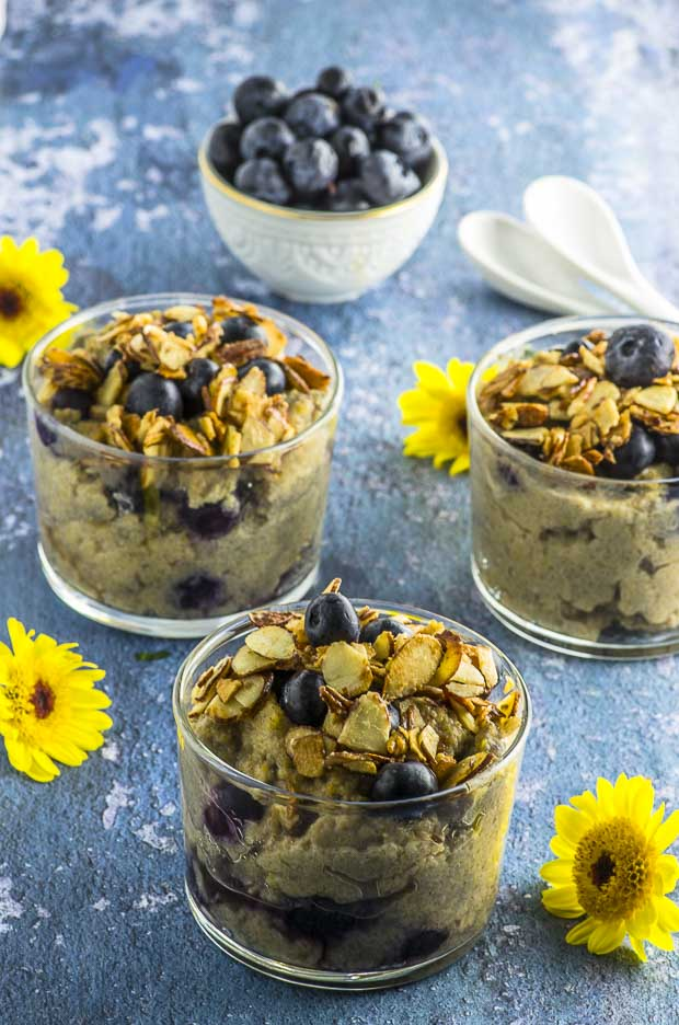 Three clear glass cups filled with blueberry muffin protein grits on a blue surface with some yellow flowers scattered and a small white bowl of blueberries in the background
