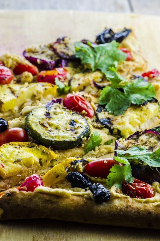 For this Hummus and Grilled Vegetable Pizzarecipe, we marinated zucchini, yellow squash and Japanese eggplant in olive, lemon, garlic, coriander, cumin and ginger. We spread a store bough crust with our home made hummus, instead of cheese for a healthy twist.
