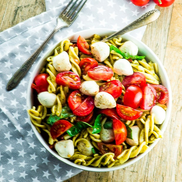 Birds eye view of the high protein pasta salad in a white bowl over a gray cloth napkin with white starts
