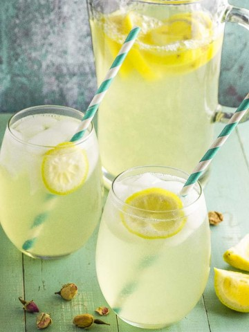 two glasses filled with rosewater lemonade and a pitcher in the background