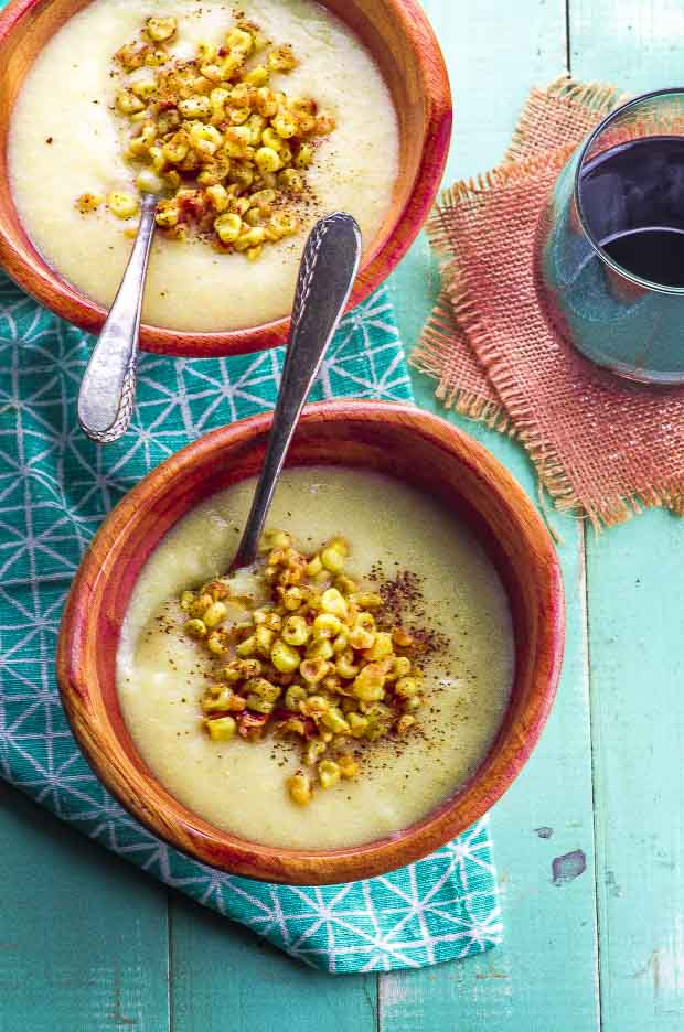 Two wooden bowls with spoons, on a blue and white napkin, filled with vegan creamy corn soup, topped with sauteed corn kernels and ground black pepper
