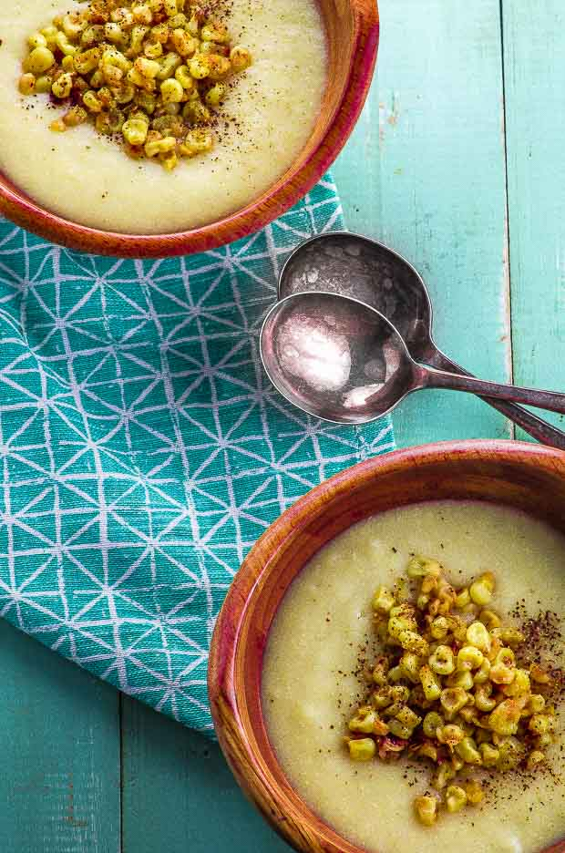 Two wooden bowls on a blue and white napkin, filled with vegan creamy corn soup, topped with sauteed corn kernels and ground black pepper, with two spoon in between the bowls