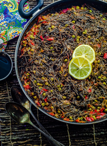 """This High Protein Noodle Paella is a vegan version of a popular Spanish dish called """"Fideua"""", traditionally made with fish and shellfish. Vegetarian Black Bean Noodles in a paella pan with vegetables with a couple of slices of lemon."""