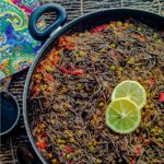 "This High Protein Noodle Paella is a vegan version of a popular Spanish dish called ""Fideua"", traditionally made with fish and shellfish. Vegetarian Black Bean Noodles in a paella pan with vegetables with a couple of slices of lemon."