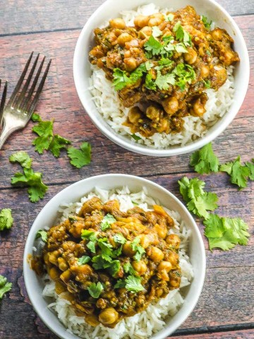 Two white bowls filled with rice topped with chickpea curry , placed in a wooden surface and with pieces of cilantro leaves scattered around