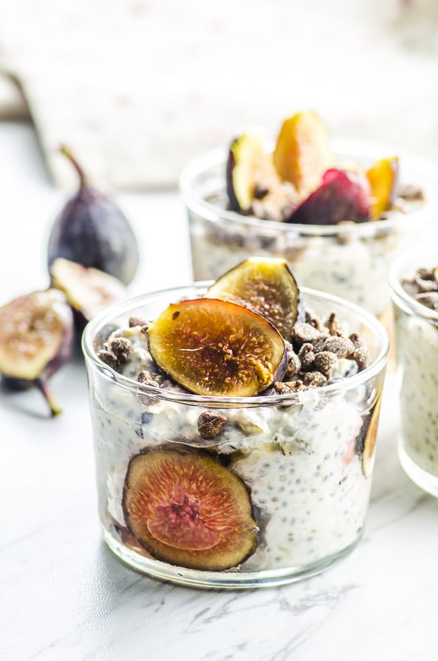 2 glass cups filled with easy overnight oats with figs slices and mini chocolate chips, on top of a white surface with a fig sliced in haldf and a whole fig in the background