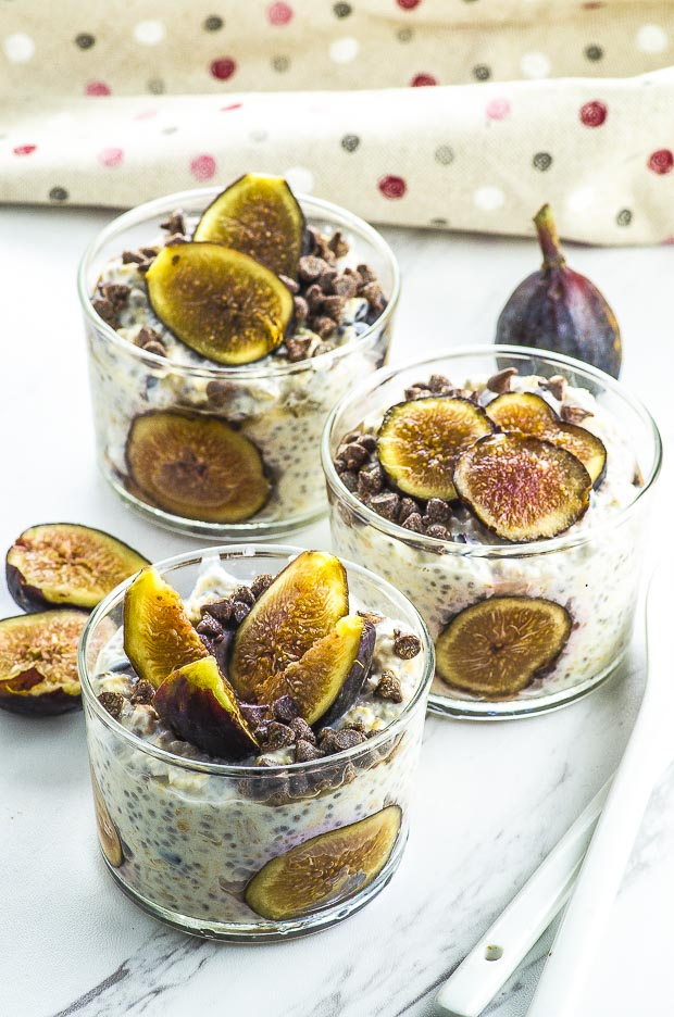 3 cups filled with easy overnight oats with figs slices and mini chocolate chips, on top of a white surface with a fig sliced in half on the left side, a whole fig on the right and a brown napkin with polkadots in the back