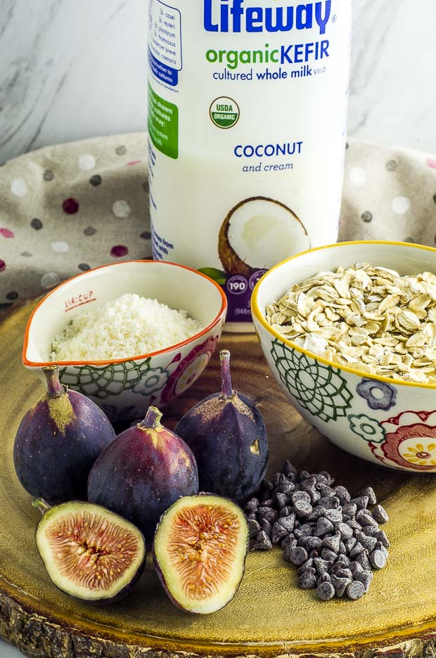 Ingredients for Easy overnight oats with figs and coconut. Oats and shredded coconut in white bowls with green, red and orange pattern, mini chocolate chips and 3 whole figs and one cut in half, on a round wooden board. A bottle of Lifeway coconut Kefir in the backgroundd