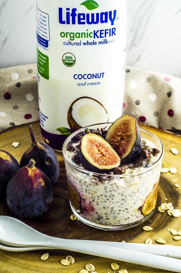 A glass cup with easy overnight oats with figs slices and mini chocolate chips on top, 2 white ceramic spoons next to 3 whole figs and a bottle of Lifeway coconut kefir on a round wooden board.
