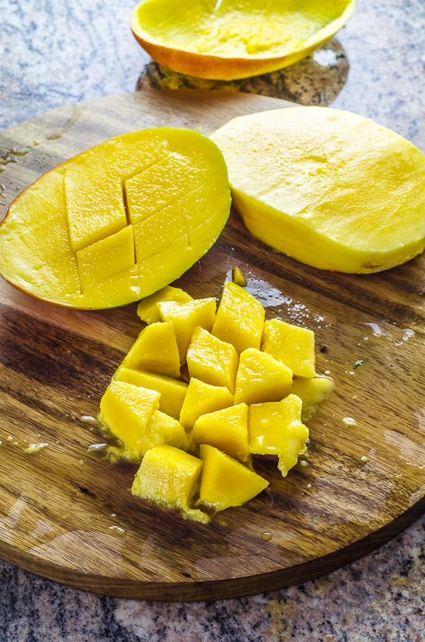 One slice of mango scored, one mango pit and diced mango on a wooden cutting board