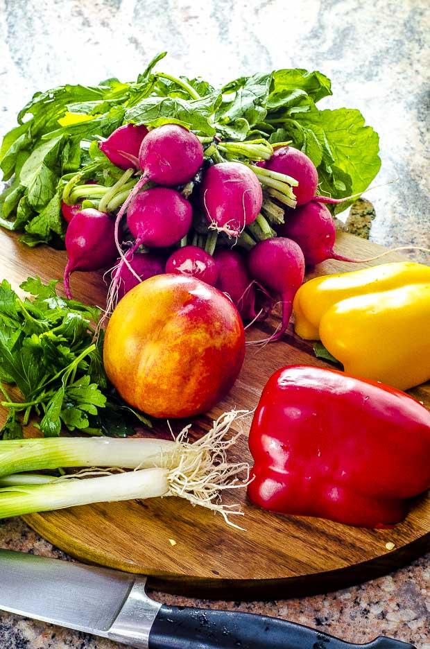 Red and yellow pepper, nectarine, whole scallions, cilantro and radishes on a wooden board with a knife on the side