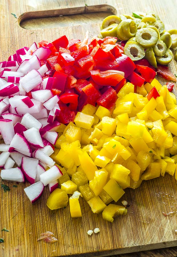 Diced red and yellow peppers and radishes, slices olives on a wooden board