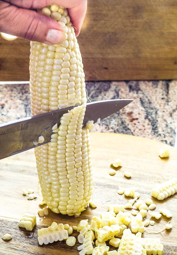 Corn kernels being cut off an ear on corn with a knife