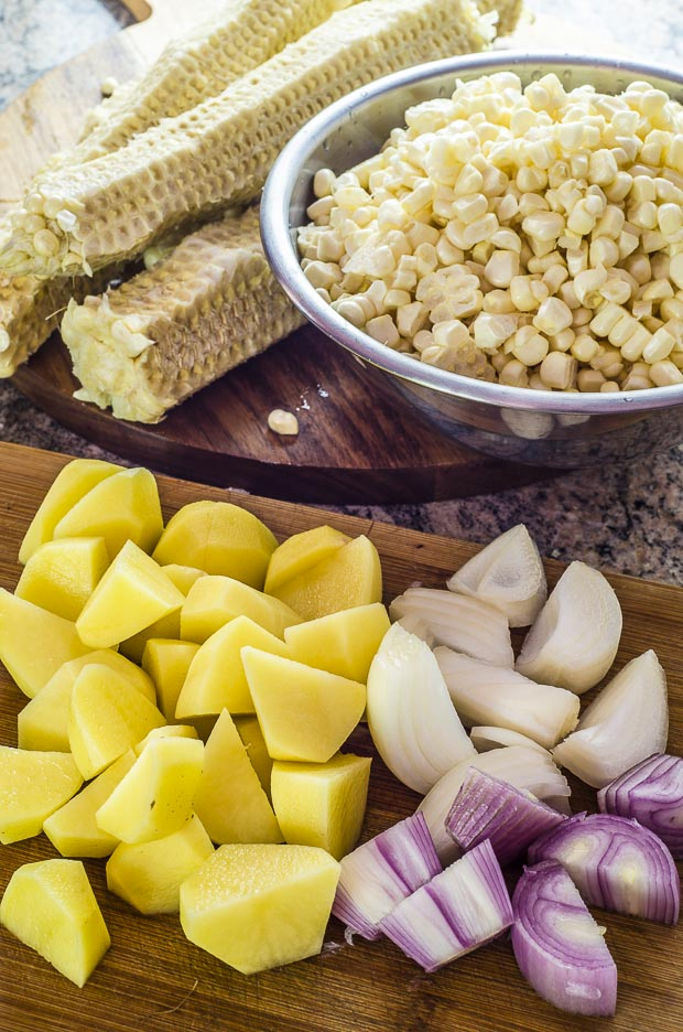 Diced potatoes and onions on a wooden cutting board. Stainless steel bowl with corn kernels
