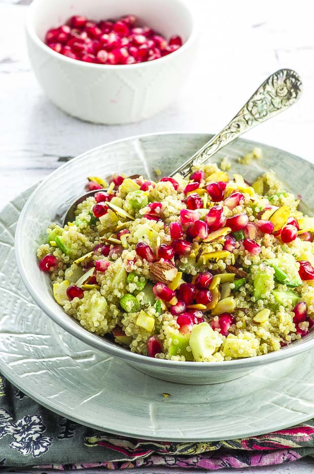A light grey bowl with quinoa pomegranate salad, with an ornate metal spoon and a small white bowl with pomegranate seeds in the background
