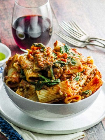 A white bowl over filled with rigatoni pasta topped with an easy lentil bolognese and a few baby spinach leaves . The bowl in placed on top of a white plate, under the plate there is a white napkin with a blue fringe. on the background there is a glass of wine, 3 forks and a sliver view of a small white bowl with olive oil.