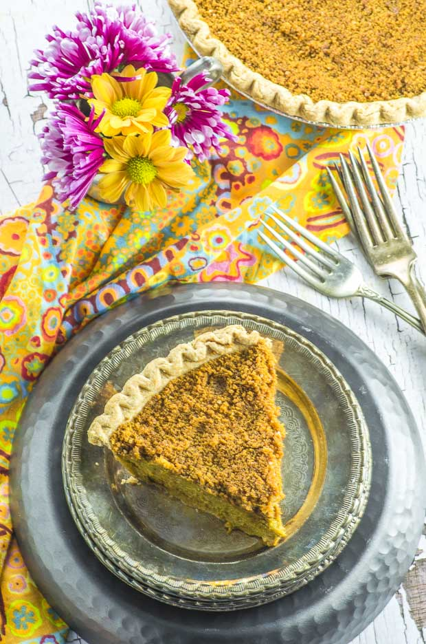 Birds eye view of a slice of Ginger Snap Vegan Pumpkin Pie on a small silver plate, on top of a larger black plate, over an orange flower patterned napkin, with two forks placed on the right hand side. In the bakground is the rest of the pie and a small flower pot with yellow and pink flowers