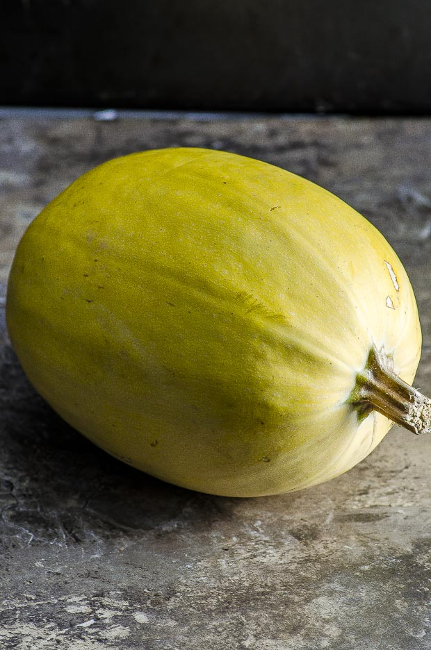 A spaghetti squash on a brown marble surface
