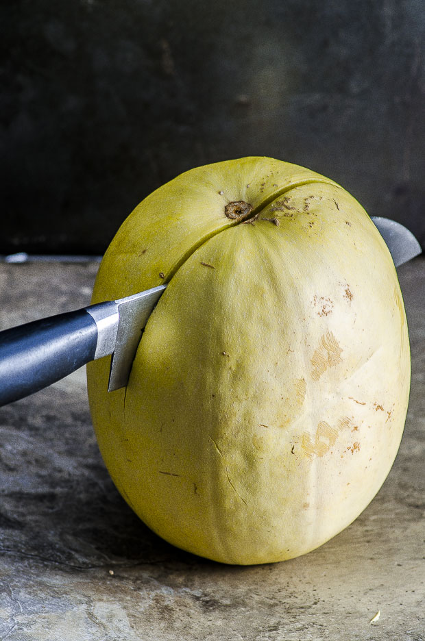 A large spaghetti squash standing vertically with a knife cutting through it