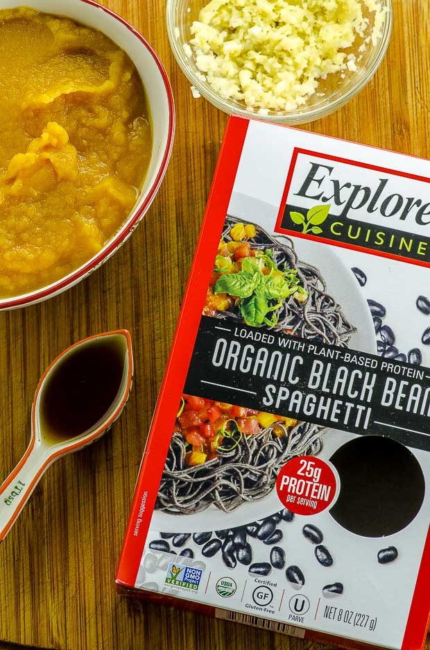 A box of Explore Cuisine black bean noodles, a small glass bowl with grated ginger above it, a white bowl with butternut squash puree and a tablespoon of tamari sauce on the left side on a wodden board
