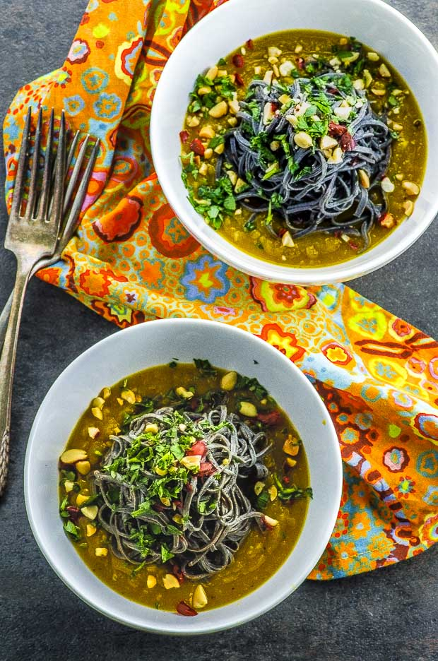 Two white bowls with black bean noodles with butternut squash sauce topped with chopped peanuts and cilantro on a black surface. Between the two bowl there is a printed orange yellow and red napkin and two forks stacked