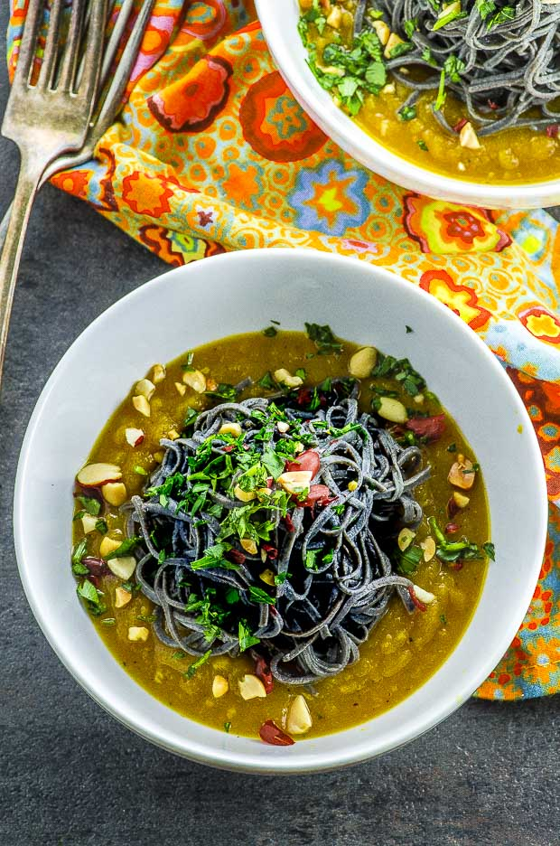 Birds eye view of one white bowl filled with black bean noodles over butternut squash sauce, on a gray surface with an orange napkin with flower pattern