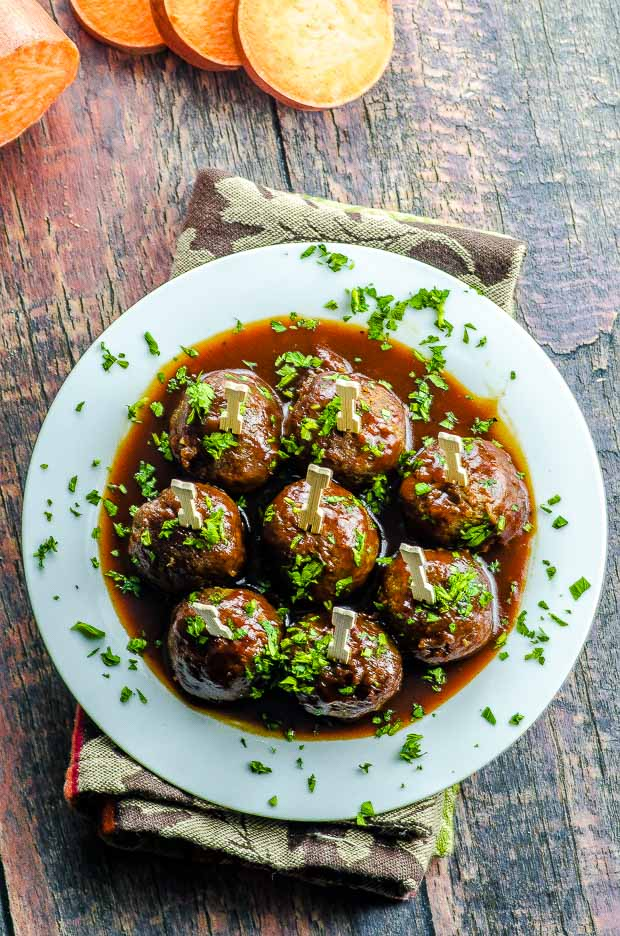 Birds eye view of the sweet potato veggie meatballs with barbeque sauce placed on a white serving platter with toothpicks and chopped parley on top, over a reddish wooden surface.